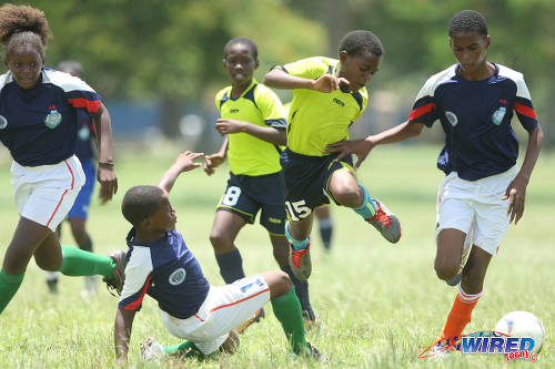 Photo: Trendsetter Hawks standout Luke Williams (centre) hurdles a tackle against Santa Cruz in an Under-13 contest of the 2015 Republic Bank National Youth Cup in the Queen's Park Savannah.  (Courtesy Allan V Crane/Wired868)