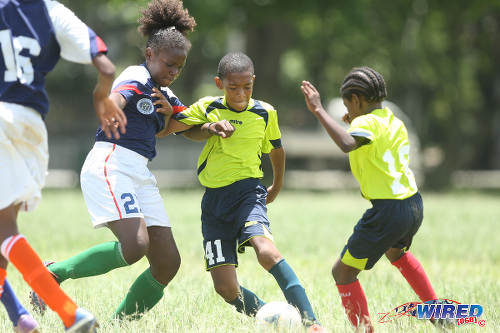 Photo: Trendsetter Hawks Under-11 midfielder Josiah Wilson (centre) tries to shake off attention from a Santa Cruz FA player (left) during 2015 Republic Bank National Youth Cup Under-13 action at the Queen's Park Savannah.  (Courtesy Allan V Crane/Wired868)