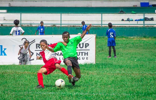 Photo: A San Juan Jabloteh player (left) battles for possession with a La Horquetta opponent during their Republic Bank National Youth Cup Under-11 quarterfinal fixture. (Courtesy Amigo Garraway/Republic Bank)
