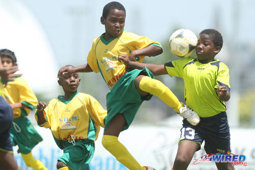 Photo: A Memphis FC player (centre) gives the boot to a Trendsetter Hawks opponent during North Zone Under-11 action at the 2015 Republic Bank Youth Cup in the Queen's Park Savannah.  (Courtesy Allan V Crane/Wired868)
