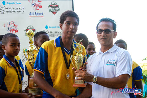 Photo: SKHY FC striker Justin Araujo-Wilson (centre) collects the Under-13 MVP trophy from Republic Bank Risk Department manager Vijay Ragoonanan. (Courtesy Sinead Peters/Wired868)