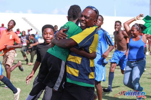 Photo: Uprising Youths coach Sheldon Mitchell (centre) hugs an Under-11 player, after their penalty shoot out win over San Juan Jabloteh. (Courtesy Sinead Peters/Wired868)