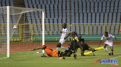Photo: Defence Force midfielder Jerwyn Balthazar (second from left) knocks an equalising goal past St Ann's Ranger goalkeeper Stefan Berkeley (far left) in 2015/16 Pro League action. (Courtesy Chevaughn Christopher/Wired868)