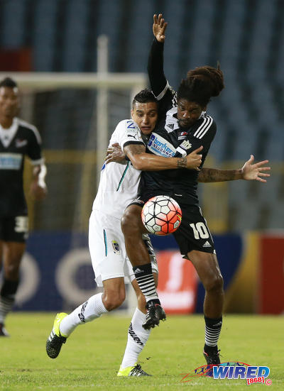 Photo: Comunicaciones midfielder Jorge Aparacio (left) grapples with Central FC star Marvin Oliver during 2015 CONCACAF Champions League action. (Courtesy Allan V Crane/Wired868)