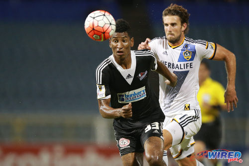 Photo: Central FC striker Willis Plaza (left) keeps his eye on the ball while LA Galaxy defender Tommy Meyer trails during 2015 CONCACAF Champions League action. (Courtesy Allan V Crane/Wired868)