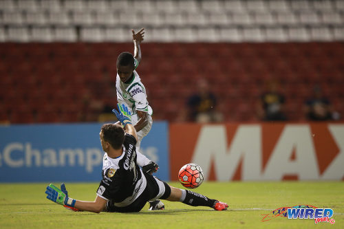 Photo: Santos Laguna goalkeeper Agustin Marchesin uses his right leg to block a shot from W Connection attacker Dimitrie Apai during CONCACAF Champions League action. (Courtesy Allan V Crane/Wired868)