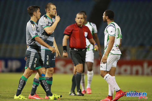Photo: Santos Laguna defenders Kristian Alvarez (centre) and Javier Abella (left) gesture at W Connection attacker Shahdon Winchester (right) while referee Baldomero Toledo looks on during 2015 CONCACAF Champions League action at the Hasely Crawford Stadium, Port of Spain. (Courtesy Allan V Crane/Wired868)