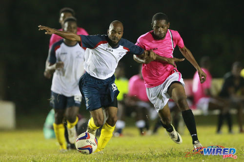 Photo: Edinburgh 500 defender Kelonne Cazoe (left) tries to hold off Malabar FC attacker Mikheil Peters during a previous CNG National Super League Championship Division contest at D'abadie Recreation Grounds.  (Courtesy Allan V Crane/Wired868)