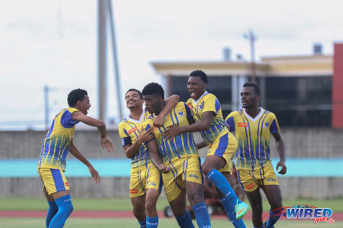 Photo: Fatima College's Mosiah Griffith (center) is congratulated by teammates after his goal today against Presentation College (San Fernando) in SSFL Premier Division action. (Courtesy Wired868)