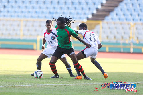 Photo: San Juan Jabloteh midfielder Keyon Edwards (centre) holds off Morvant Caledonia United players Kareem Knights (right) and Jameel Neptune during Pro League action yesterday. (Courtesy Chevaughn Christopher/Wired868)