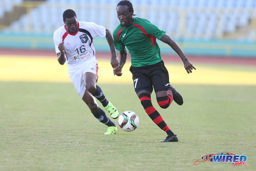Photo: San Juan Jabloteh winger Nathan Lewis (right) races past Morvant Caledonia United right back Ordell Flemming in 2015 Pro League action. (Courtesy Chevaughn Christopher/Wired868
