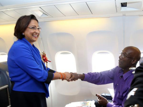 Photo: Prime Minister Kamla Persad-Bissessar (left) shakes hands with Opposition Leader Dr Keith Rowley en route to Nelson Mandela's funeral in South Africa. (Courtesy News.Gov.TT)