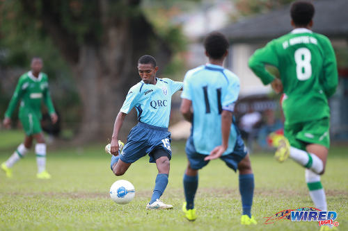 Photo: QRC attacker John-Paul Rochford (centre) takes a crack at goal during 2015 SSFL action against St Augustine Secondary. Rochford is expected to be a key member of the Trinidad and Tobago National Under-17 Team. (Courtesy Allan V Crane/Wired868)