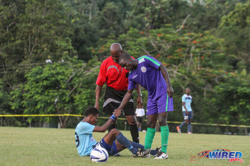 Photo: Real Maracas winger Gabriel Ragout (sitting) is helped to his feet by a Club Sando player during NSL action yesterday in Maracas. (Courtesy Sinead Peters/Wired868)