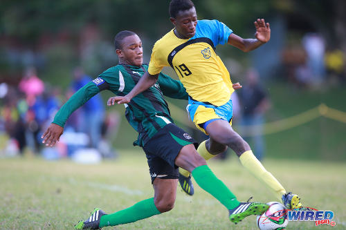 Photo: Carapichaima East Secondary's Cadiz Chandler (left) tackles Speyside High School's Shaffie McKenzie during SSFL Premier Division action today in Speyside, Tobago. (Courtesy Allan V Crane/Wired868)