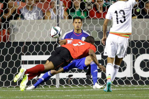 Photo: Trinidad and Tobago forward Jonathan Glenn (foreground) heads past Mexico goalkeeper Alfredo Talavera during Friday's friendly 3-3 draw in Utah. (Courtesy TTFA)