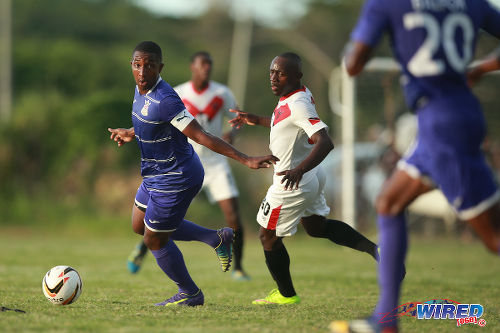 Photo: Defence Force captain Chris Durity (left) looks for passing options while Tobago FC Phoenix 1976 player Onasi Forde (centre) looks on during 2015/16 CNG National Super League action at the Canaan Recreational Grounds, Tobago. (Courtesy Allan V Crane/Wired868)