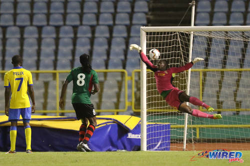 Photo: Defence Force custodian Sheldon Clarke (right) makes a vain effort to block a free kick from San Juan Jabloteh's Tyrone Charles in First Citizens Cup action last night. Looking on is Jabloteh's Keyon Edwards (centre) and Defence Force's Jelani Felix. (Courtesy Chevaughn Christopher/Wired868)