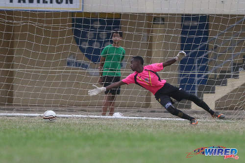 Photo: St Benedict's College goalkeeper Jabari Gray dives in vain after an effort from Fatima College attacker Sebastien Camacho, during a 2015 SSFL contest. The shot crept just wide. (Courtesy Chevaughn Christopher/Wired868)