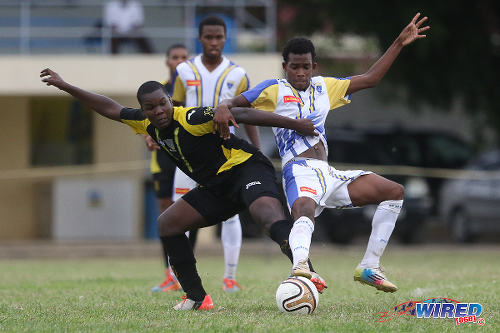 Photo: St Benedict's College midfielder Tyrik Eastman (left) tussles for possession with Fatima College midfielder Kyon Williams during 2015 SSFL action. (Courtesy Chevaughn Christopher/Wired868)