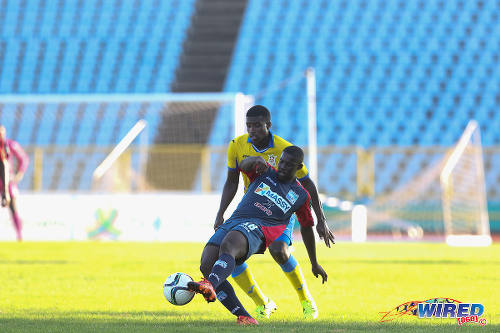 Photo: Morvant Caledonia United midfielder Akeem Roach (foreground) passes the ball while Defence Force midfielder Dave Long looks on in 2015 First Citizens Bank action. (Courtesy Chevaughn Christopher/Wired868)