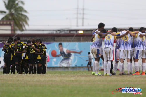 Photo: The Fatima College (right) and St Benedict's College players huddle before kick off in 2015 SSFL action at Mucurapo Road. (Courtesy Chevaughn Christopher/Wired868)