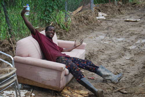 Photo: A Diego Martin looks on the brighter side in the aftermath of flooding. (Copyright TTNewsFlash)