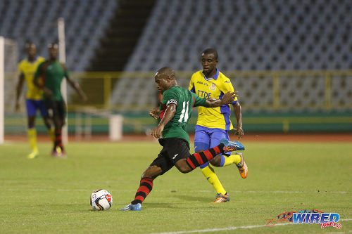Photo: San Juan Jabloteh captain Damian Williams (foreground) prepares to drive a cross into the opposing penalty area during First Citizens Cup action against Defence Force last night. (Courtesy Chevaughn Christopher/Wired868)