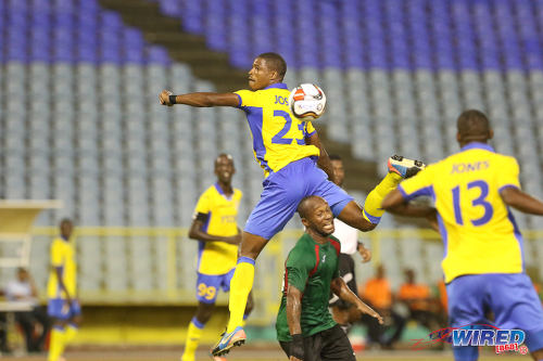 Photo: San Juan Jabloteh midfielder Kennedy Hinkson (centre) finds himself at the bottom of an aerial challenge from Defence Force winger Kerry Joseph in First Citizens Cup action last night. (Courtesy Chevaughn Christopher/Wired868)