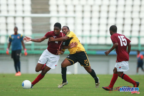 Photo: Cunupia FC attacker Andrew Tinto (centre) tries to hold on to La Horquetta SA captain Atiba Hackette (left) while teammate Kern Roberts looks on in 2015 CNG NSL Knock Out action at the Larry Gomes Stadium, Malabar. (Courtesy Allan V Crane/Wired868)