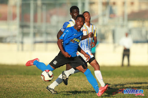 Photo: Naparima College winger Akinola Gregory (foreground) runs with the ball during SSFL action today against Fatima College. (Courtesy Allan V Crane/Wired868)
