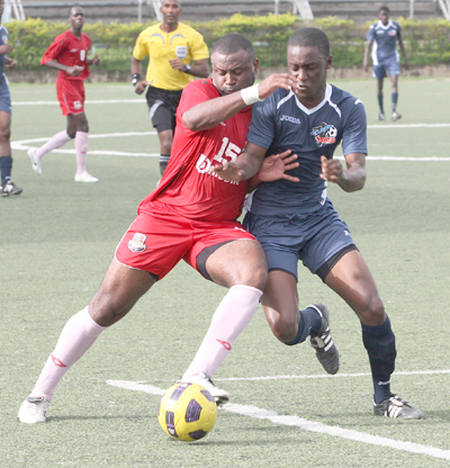 Photo: Former Joe Public attacker Brent Antoine (left) tussles with Club Sando player Devon Bristol in this Trinidad Guardian file photo.  Antoine, who represented Prisons in recent seasons, passed away on October 1. (Copyright Trinidad Guardian)