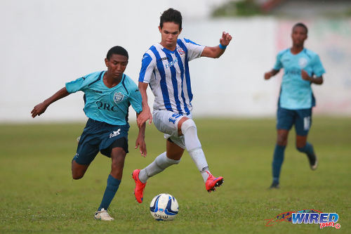 Photo: QRC playmaker John-Paul Rochford (left) keeps the ball from St Mary's College attacker Ethan Shim during previous SSFL action at Serpentine Road. (Courtesy Allan V Crane/Wired868)