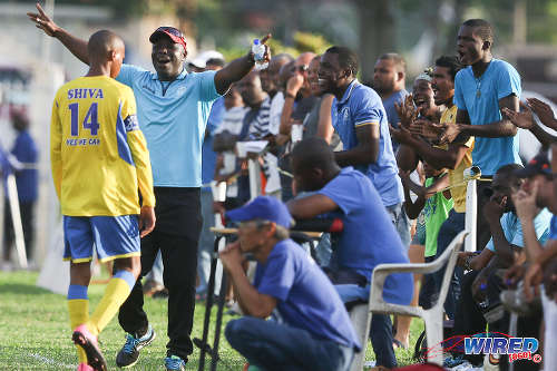 Photo: Shiva Boys HC coach Hayden Ryan (second from left) celebrates his team's third goal while St Mary's College coach Ryan Shim (stooping) looks on at Serpentine Road. (Courtesy Chevaughn Christopher/Wired868)