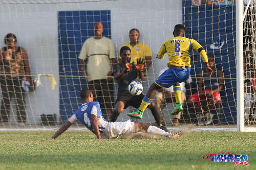 Photo: Shiva Boys HC left back Isaiah Garcia (right) blasts a shot at goal while St Mary's College goalkeeper Kristopher Donaldson (centre) prepares to save. (Courtesy Chevaughn Christopher/Wired868)