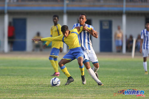Photo: Shiva Boys HC midfielder Mark Ramdeen (left) holds off St Mary's College player and fellow substitute Joshua Joseph. (Courtesy Chevaughn Christopher/Wired868)