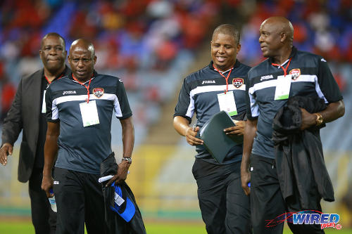 "Photo: Trinidad and Tobago National Senior Team technical staff members (from right) Michael ""Brow"" Maurice, Derek King, Hutson ""Barber"" Charles and William Wallace exchange ideas before kick off last night against Nicaragua. (Courtesy Allan V Crane/Wired868)"