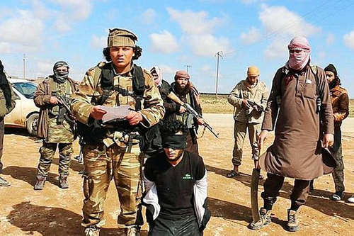 Photo: ISIS soldiers prepare to execute a hostage. (Copyright UK Mirror)