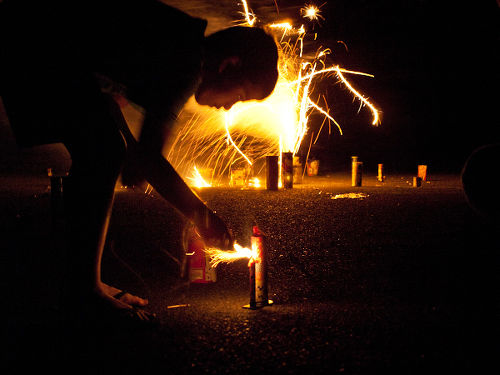 Photo: A youngster prepares to light fireworks. (Courtesy Flickr)