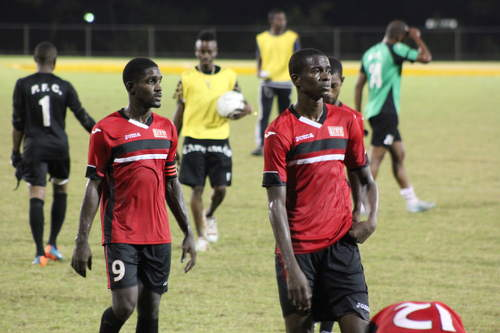 Photo: UTT striker Jamal Creighton (right) and Stefon Pierre leave the field after 2015 CNG NSL action against Prisons FC. (Copyright Anita Sidial)