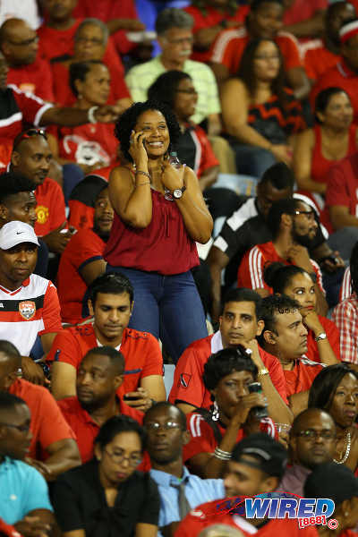 Photo: A female Trinidad and Tobago fan (centre) phones it in during a lull in action at the 2018 World Cup qualifier between Trinidad and Tobago and the United States. (Courtesy Allan V Crane/Wired868)
