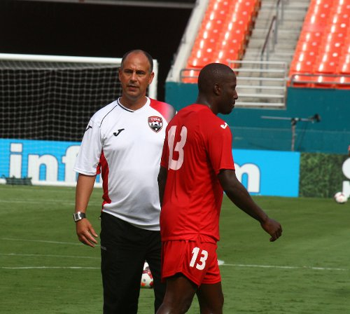 Photo: Trinidad and Tobago striker Cornell Glen (right) walks past head coach Stephen Hart during practice at the 2013 CONCACAF Gold Cup. (Courtesy TTFA Media)