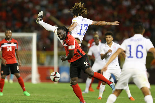 Photo: Trinidad and Tobago captain Kenwyne Jones (centre) winces after a challenge from US midfielder Jermaine Jones in 2018 World Cup qualifying action at the Hasely Crawford Stadium. (Courtesy Allan V Crane/Wired868)