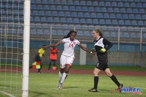 """Photo: Trinidad and Tobago star Karyn """"Bibi"""" Forbes (left) celebrates the decisive goal against Puerto Rico in the 2015 Caribbean Olympic qualifying final at the Ato Boldon Stadium in Couva. Looking on is Puerto Rico goalkeeper Karly Gustafson. Forbes' football tournament in Plymouth on Saturday created problems for the Stokely Vale team yesterday. (Courtesy Chevaughn Christopher/Wired868)"""