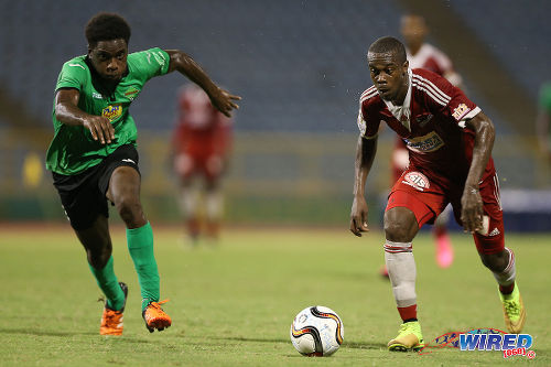 Photo: Central FC attacker Marcus Joseph (right) tries to accelerate past San Juan Jabloteh defender Garth Thomas during 2015 Pro League action last night at the Hasely Crawford Stadium. (Courtesy Allan V Crane/CA-images/Wired868)