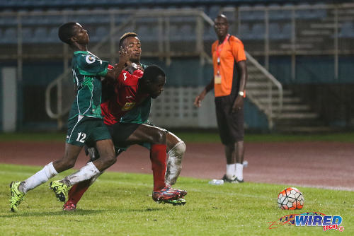 Photo: W Connection player Dimitrie Apai (left) and Kevon Goddard try to muscle San Juan Jabloteh right back Rickcardo Harriott (centre) off the ball during 2015/16 Pro League action yesterday in Couva. Looking on is Jabloteh assistant coach Nigel Henry (right). (Courtesy Chevaughn Christopher/Wired868)