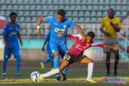Photo: Naparima College striker Isaiah Hudson (left) brushes St Anthony's College midfielder Shem Clauzel off the ball during the 2015 National Intercol final. (Courtesy Chevaughn Christopher/Wired868)