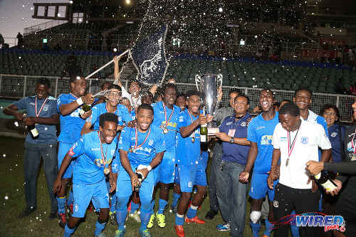 Photo: Naparima College star Jared Dass (centre) has his hand on the 2015 National Intercol trophy as the southern schoolboys celebrate at the Mannie Ramjohn Stadium. (Courtesy Chevaughn Christopher/Wired868)