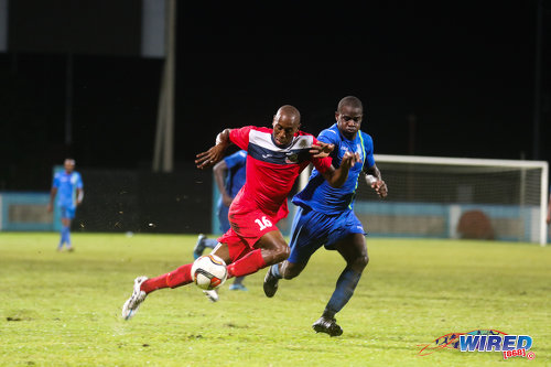 Photo: Police FC defender Elijah Belgrave (right) chases Club Sando striker Kevon Woodley during 2015/16 Pro League action yesterday evening in Couva. (Courtesy Chevaughn Christopher/Wired868)