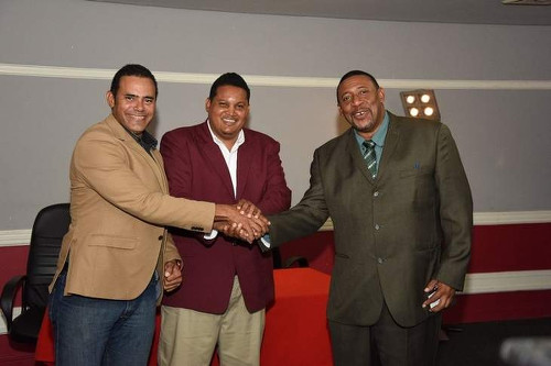Photo: TTFA president David John-Williams (right) shakes hands with SPORTT Company chairman Michael Phillips (left) while Sport Minister Darryl Smith looks on. (Courtesy TTFA Media)